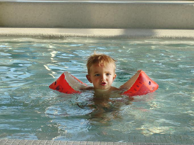 malé dítě v bazénu s červenými rukávky